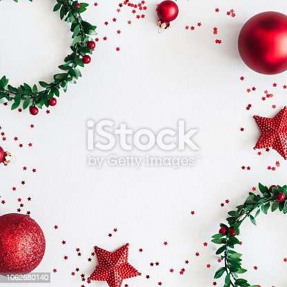 1060169304 istock photo Christmas composition. Wreaths, red decorations on pastel gray background. Christmas, winter, new year concept. Flat lay, top view, copy space, square 1062680140