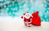 Christmas concept background of Santa claus with red bag over blurred snow flack background