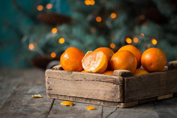 christmas concept with Tangerines, Fir , lights ,Snow, boke and snowflakes, on wooden background christmas concept with Tangerines, Fir , lights ,Snow, boke and snowflakes, on wooden background tangerine stock pictures, royalty-free photos & images