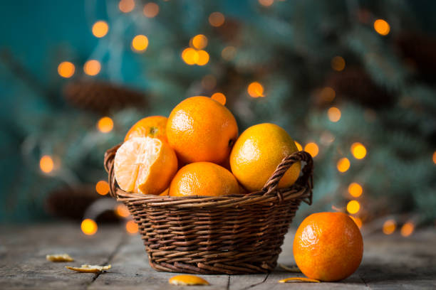 christmas concept with Tangerines, Fir , lights ,Snow, boke and snowflakes, on wooden background stock photo