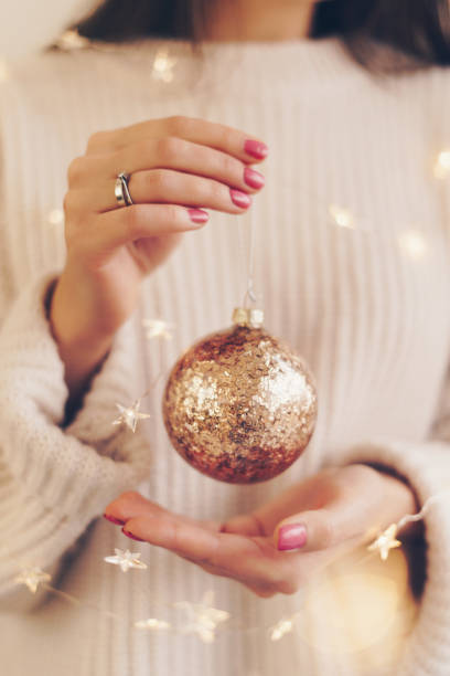 Christmas concept: woman holding Christmas decorations Christmas concept: unrecognisable woman holding Christmas decoration pink nail polish stock pictures, royalty-free photos & images
