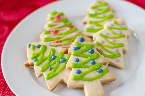 Christmas Cookie Christmas tree shaped sugar cookies decorated with icing on a white plate sugar cookie stock pictures, royalty-free photos & images