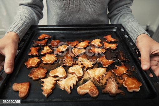 Woman hands holding baking tray with holiday cookie