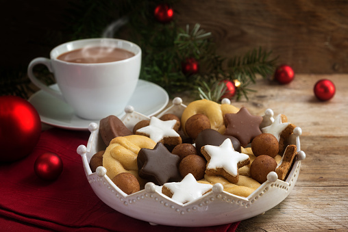 christmas cookies and a coffee cup with hot cocoa, fir tree branches and red baubles on rustic wood, cozy advent afternoon, copy space
