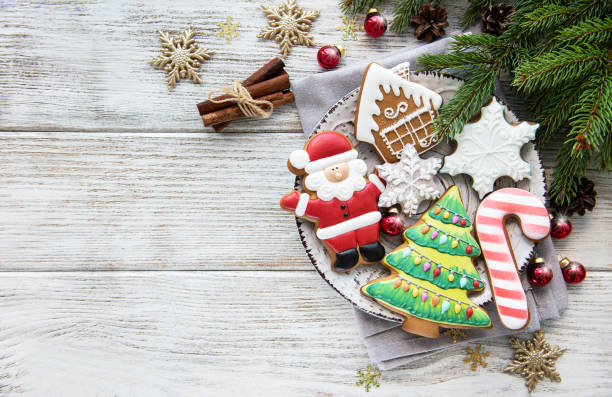 Christmas cookies and Christmas tree Christmas cookies and Christmas tree on a old wooden table cookie stock pictures, royalty-free photos & images