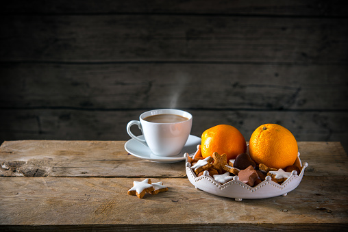 Christmas cookies and oranges in a bowl and a cup with hot coffee on a rustic table, dark wooden background with a large copy space, moody light
