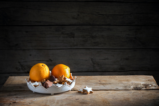 christmas cookies and oranges in a bowl on a rustic table, dark wooden background with a large copy space, moody light