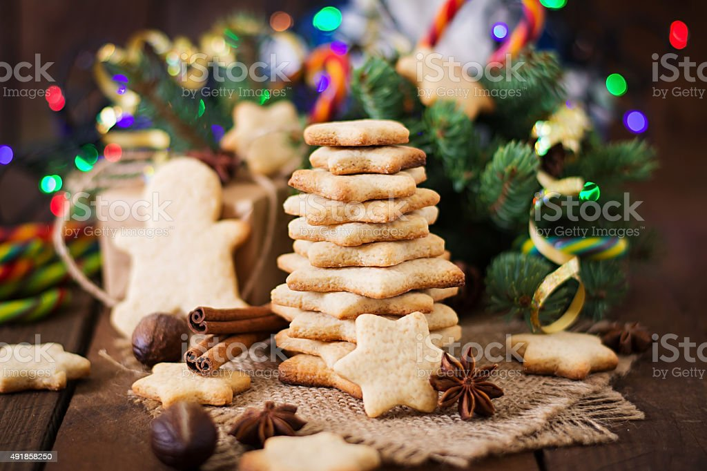 Christmas cookies and tinsel on a dark wooden background stock photo