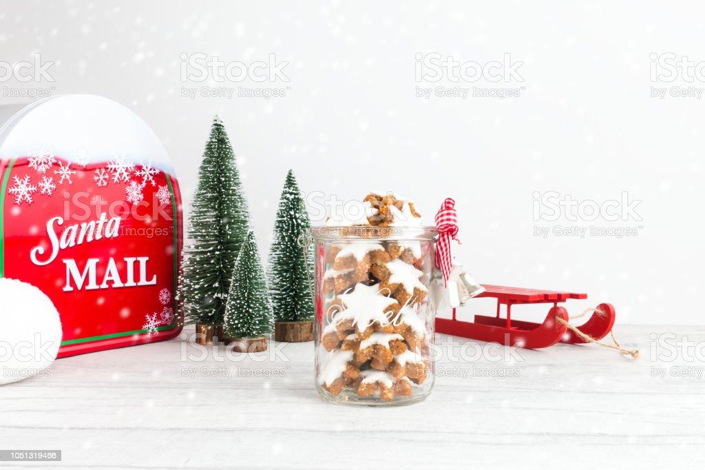 Weihnachtsplätzchen in Glas mit Schlitten, Tannen, Postfach und Schneefall – Foto