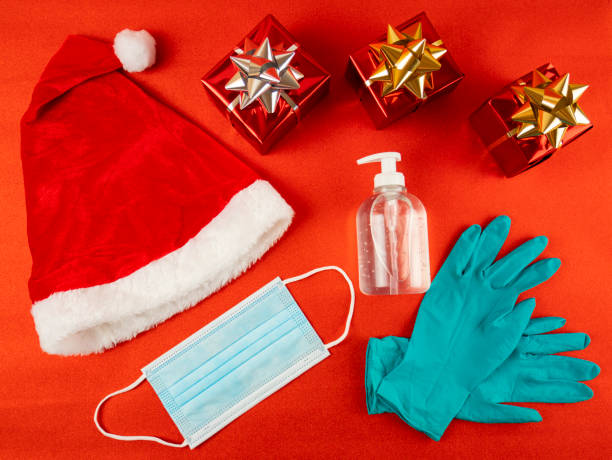 Christmas coronavirus, covid-19. Pandemic prevention kit, hand sanitizer,  protective gloves and surgical mask. Christmas gifts from santa claus on red background. Santa's red hat. View from above. stock photo