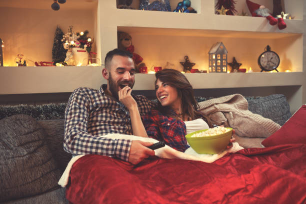 weihnachten paar aussehenden film und essen popcorn im bett - mädchen night snacks stock-fotos und bilder