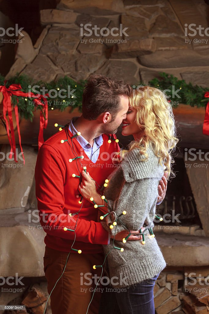 Christmas couple Affectionate couple entangled with christmas lights hugging and kissing against fireplace. Adult Stock Photo