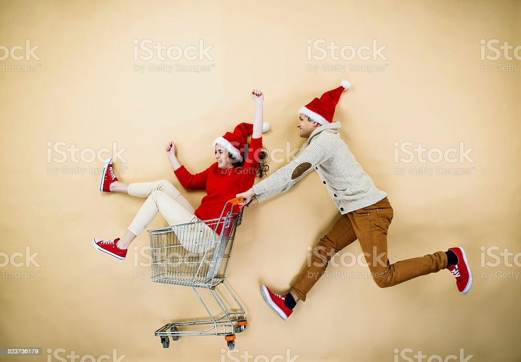 Christmas couple with trolley on beige background stock photo