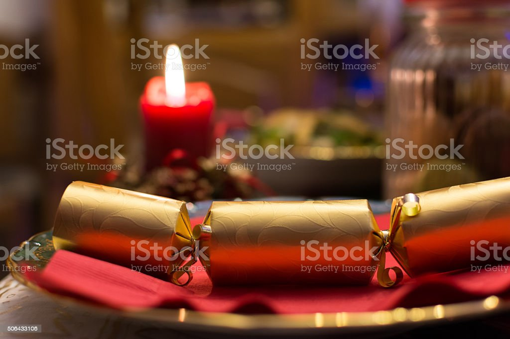 Christmas cracker on a plate with a candle on the background stock photo