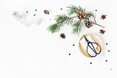 istock Christmas craft composition. Decorative corner made. Pine branch with cones, silk ribbons, vintage scissors on wooden plate, black confetti and anise stars. White table background. Flat lay, top view 1060977952
