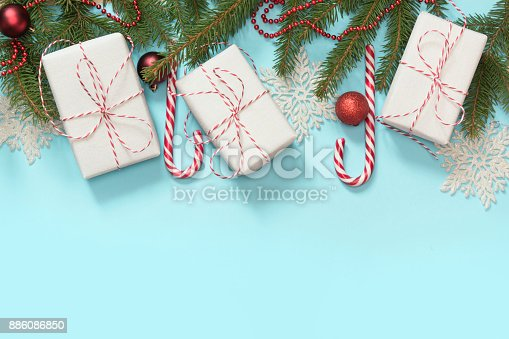 istock Christmas creative border with white and red decor, gifts, candy cane, snowflakes on blue background. Flat lay. Top view. Copy space. 886086850