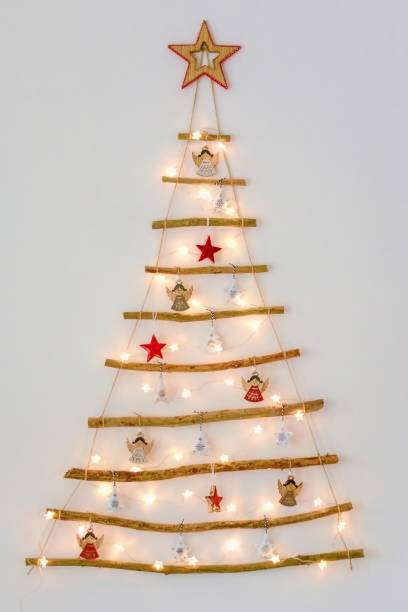 Christmas creative decoration - homemade wooden hanging christmas tree on the wall stock photo