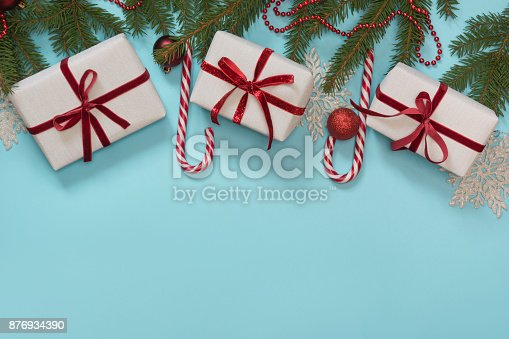 istock Christmas creative gift box wrapped with red ribbon, pack paper composed on blue. Flat lay. Top view. Creative hobby. 876934390