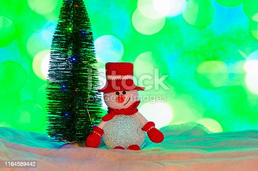 Crocheted Christmas snowman with a Christmas tree and blurred lights in the background