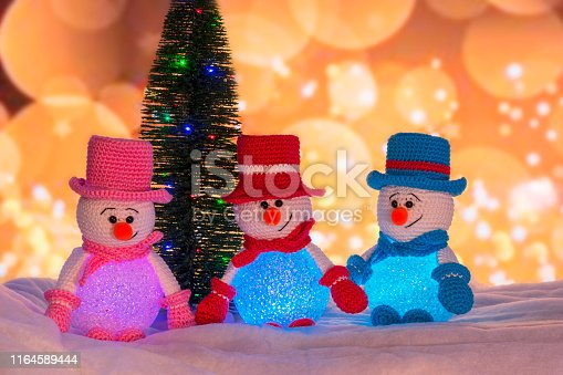Crocheted Christmas snowmen with a Christmas tree and blurred lights in the background