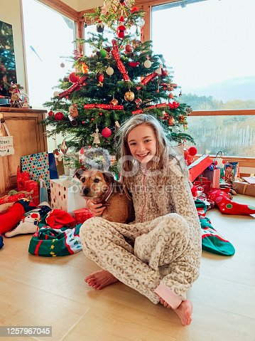 A front view, full length shot of a young girl wearing her pyjamas on Christmas morning and smiling towards the camera alongside her dog.