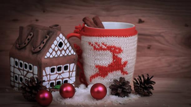 Weihnachtsbecher und ein Lebkuchenhaus auf einem Holztisch. – Foto