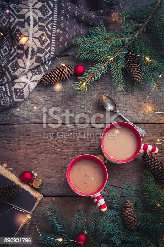istock Christmas cups of coffee cocoa with knitted sweater and a book and branche of fir tree Flat lay Top view 890931796