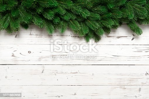istock Christmas decor with fir branches on white wooden board 1071660956