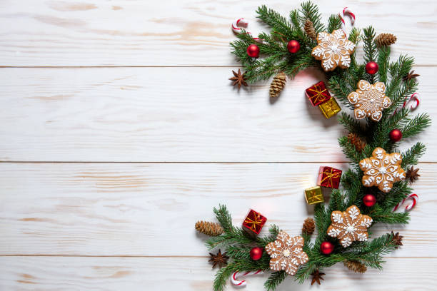 Decoração do Natal com filiais da fir-árvore e bolinhos do gengibre em um fundo de madeira branco, vista superior - foto de acervo