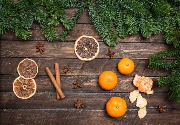Weihnachts-Dekor mit Mandarinen, getrocknete Orangenscheiben, Anis, Zimtstangen, Zweig der Fichte auf eine Holzoberfläche. – Foto