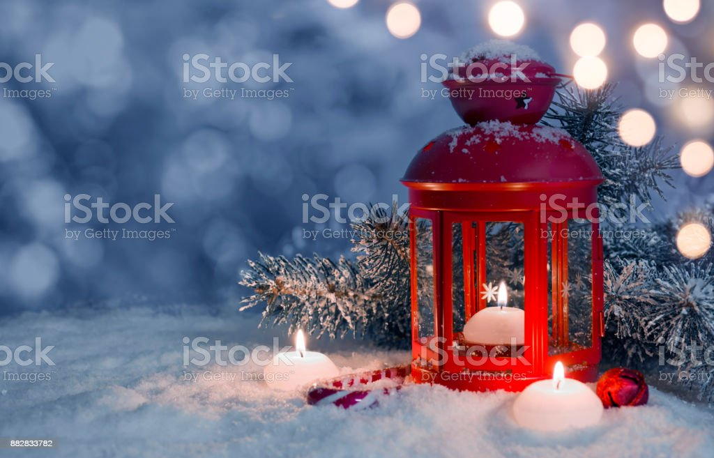 Christmas decorated lantern and candles on snow with copy space stock photo