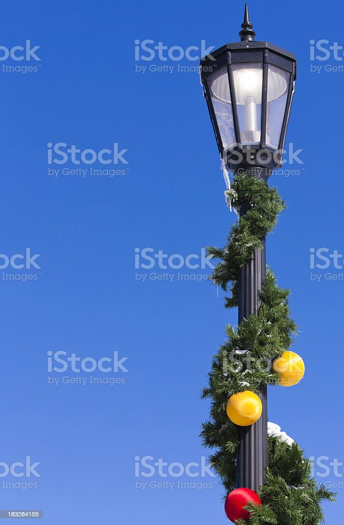 Christmas decorated snowy garland on street lamp post royalty-free stock photo