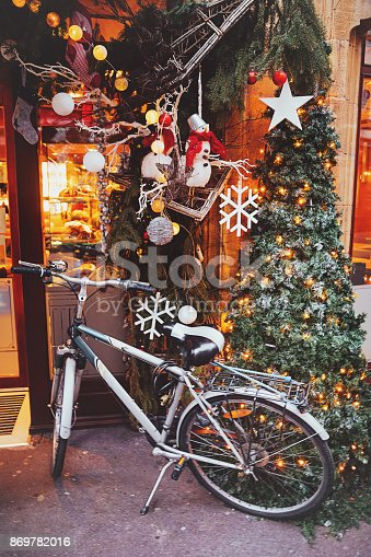 A retro bike parked in a street at illuminated Christmas ornates and lights at noel time in Colmar, Alsace, France.