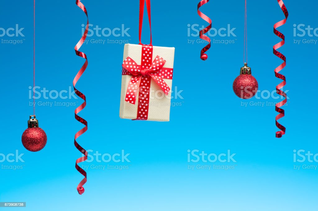 Christmas decoration and gift box hanging on blue background stock photo