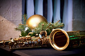 Christmas decoration and golden saxophone on wall background.