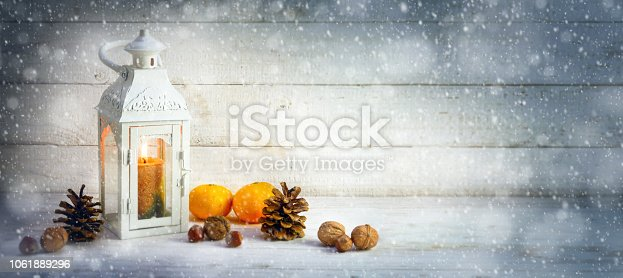 istock christmas decoration background with a candle light lantern, tangerines, cones and nuts in the snow on bright rustic wood, panoramic format with copy space 1061889296