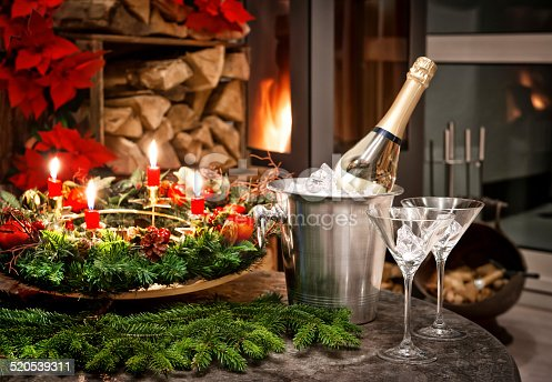 873264516istockphoto christmas decoration. bottle of champagne, glasses and fireplace 520539311
