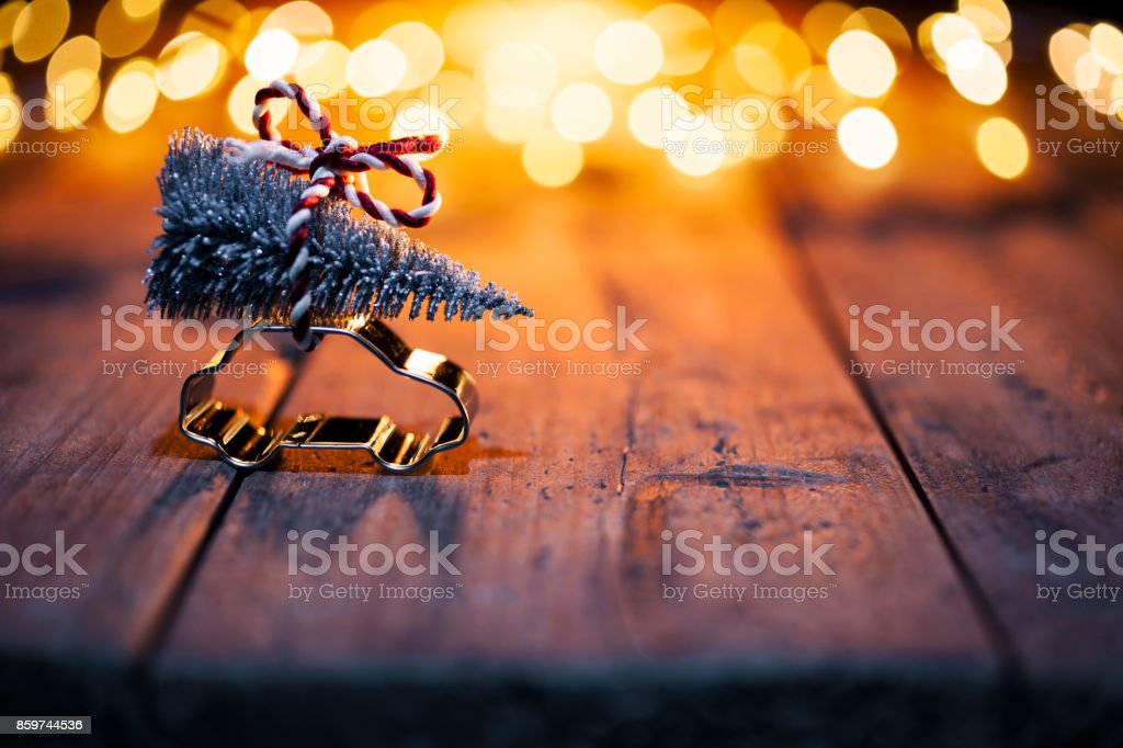 Christmas decoration - Car cutter with fir tree on old wood and defocused lights stock photo