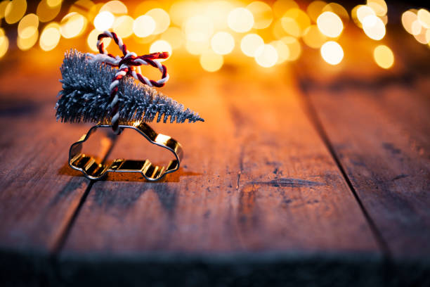 Christmas decoration - Car cutter with fir tree on old wood and defocused lights Car cutter with fir tree and christmas bow on wood cookie cutter stock pictures, royalty-free photos & images