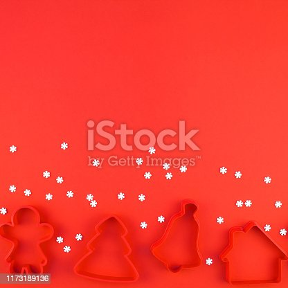 Christmas composition. New Year or Christmas flat lay top view Xmas holiday 2020 cookies cutters set on red paper background with copyspace. Template mockup greeting card text design