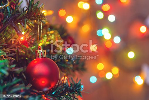 Christmas decoration. Hanging red balls on pine branches christmas tree garland and ornaments over abstract bokeh background with copy space