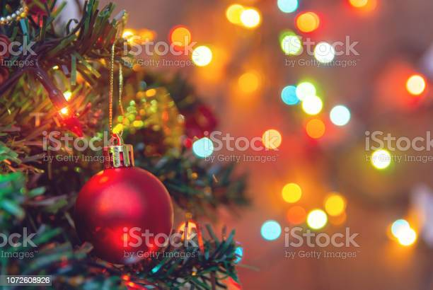 Photo of Christmas decoration. Hanging red balls on pine branches christmas tree garland and ornaments over abstract bokeh background with copy space