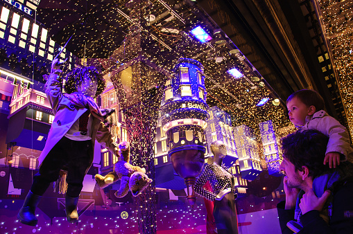 Christmas decoration in windows of Printemps department store attracts people.