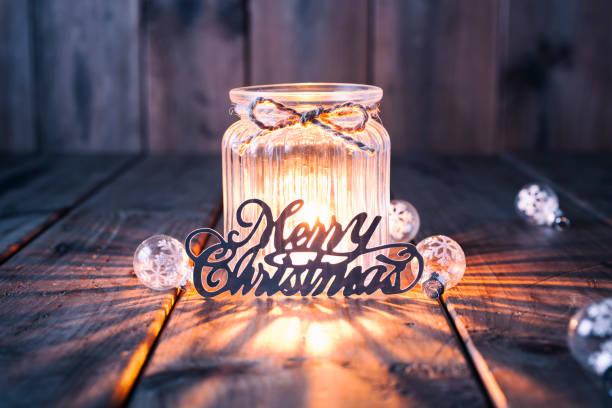 weihnachtsdekoration auf altem holz - kerze jar karte - gute nacht text stock-fotos und bilder