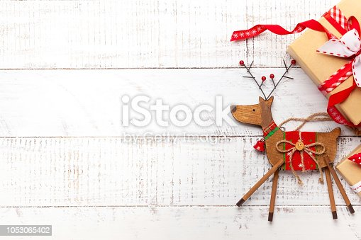 Christmas decoration and gift boxes on white wooden background.