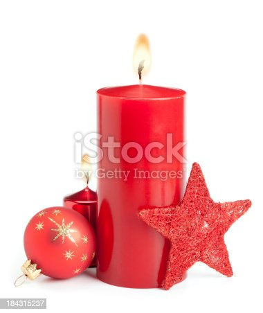 Red candles and baubles on white background. This File is cleaned, retouched and contains