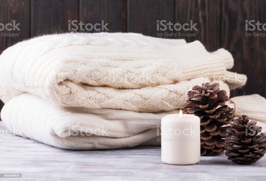 Christmas decoration. Pile of warm sweater, candle and cones. stock photo
