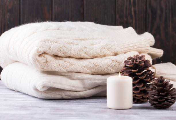 christmas decoration. pile of warm sweater, candle and cones. - caxemira imagens e fotografias de stock