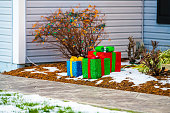 istock Christmas decoration presents in single family residential suburbs house home garden and lights on bush in northern Virginia with snow covered sidewalk road 1330600187