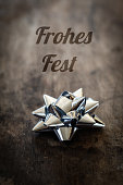 istock Christmas decoration, ribbon on wood, German wishes, Frohes Fest 498460362